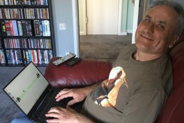 man sitting next to a laptop