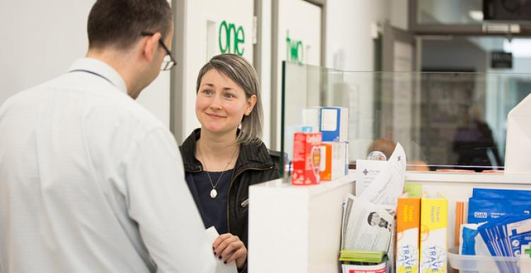 Woman picking up a prescription at chemist's