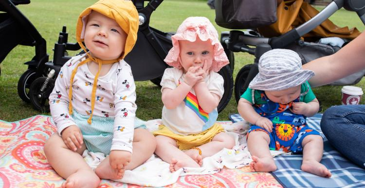 Three babies at a picnic in the park sitting on a blanket