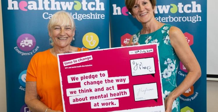 Two women holding a mental health support pledge