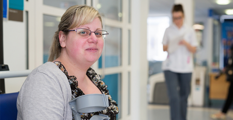 woman waiting in hospital corridor holding crutches