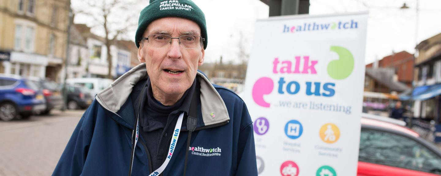 Healthwatch volunteer standing in front of a Healthwatch sign saying 'talk to us'.