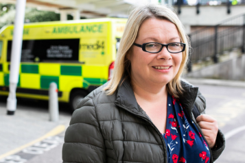 woman at hospital with ambulance in background