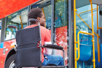 man in wheelchair waiting to board a bus