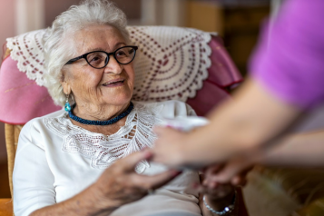 elderly woman at a care home welcomes a visitor