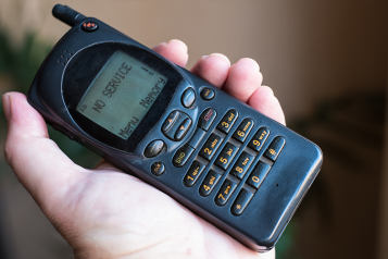 """Picture shows old style mobile phone with the words """"no service"""" on screen"""