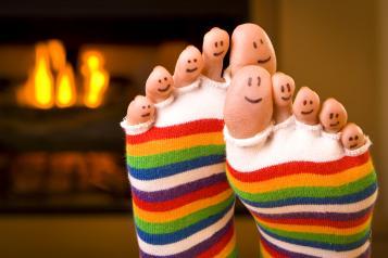 Picture shows feet in socks in front of a fire