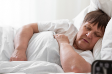 Woman sleeping in bed during day