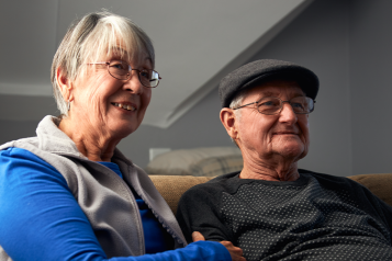 Picture shows older couple sat on sofa at home