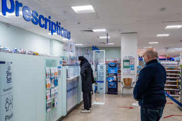 people queuing for prescriptions at a pharmacy