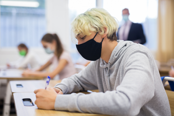 Boy in classroom wearing face covering
