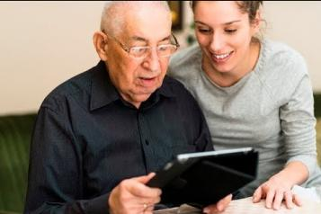 young woman and older man looking at tablet screen