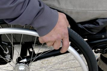 man's hand on a wheelchair wheel