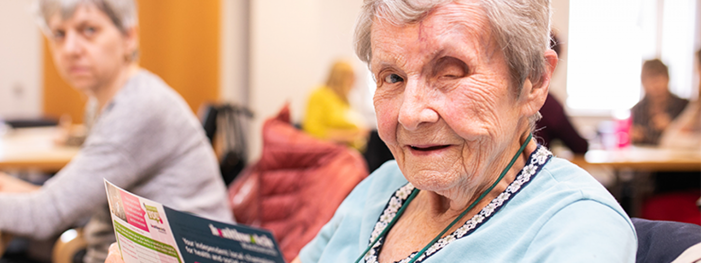 older woman holding Healthwatch leaflet and looking at camera