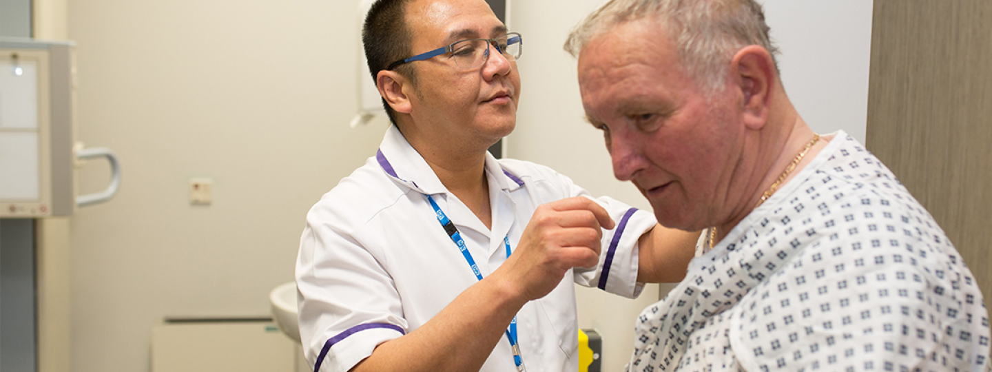 Picture of man in patient gown with an NHS radiographer